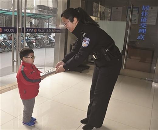 Cậu bé Mộc Mộc nộp chiếc ví nhặt được cho cảnh sát trực ban. (Ảnh: Internet)