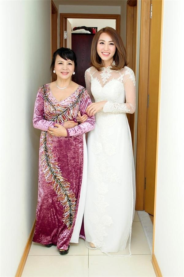 Ngân Khánh lại cách điệu bộ áo dài cưới màu trắng của mình bằng chi tiết cúp ngực đặc trưng của váy cưới hiện đại. Bộ áo dài vẫn sử dụng voan, ren, lưới làm chất liệu chủ đạo.
