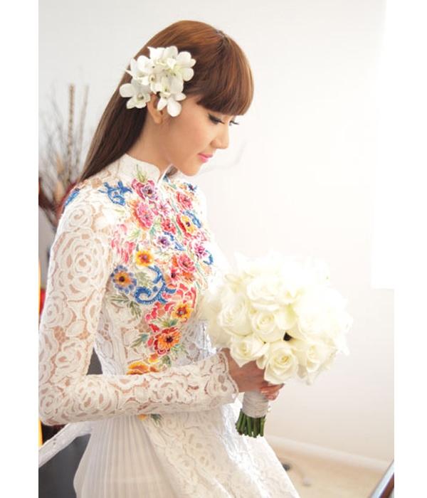 Bộ áo dài của Ngọc Quyên kết hợp hài hòa chất liệu ren mỏng cùng vải lụa xếp li điệu đà. Phần trên thân áo trở nên nổi bật nhờ những họa tiết hoa đính kết nhiều màu sắc.