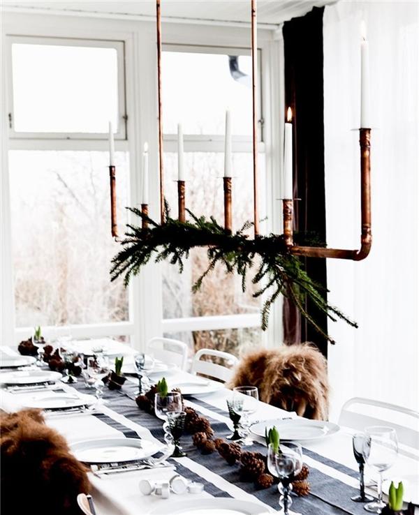 8. Thay vì thắp nến trên bàn tiệc, hãy thử biến tấu với nến được thắp trên ống nước công nghiệp thả từ trần xuống, kèm theo vài nhành lá thông tạo màu xanh cho không gian Giáng sinh.