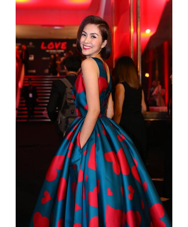 Tăng Thanh Hà điệu đà, gợi cảm với dáng váy xòe cổ điển xẻ ngực sâu. Thiết kế sử dụng hiệu ứng tương phản giữa hai tông màu xanh lam và hồng đỏ.
