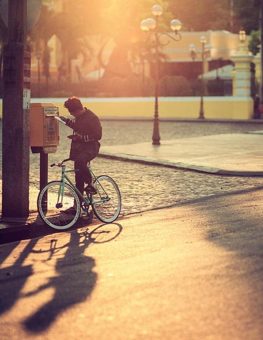 """Bức ảnh """"Năm 2015 Sài Gòn còn có người đi xe đạp gửi thư tay"""" ghi lại khoảnh khắc đời thườngcủa một chàng trai đi xe đạp đến bưu điện gửi thư giữa phố Sài Gònkhiến nhiều người bồi hồi và thích thú. (Ảnh: Internet)"""
