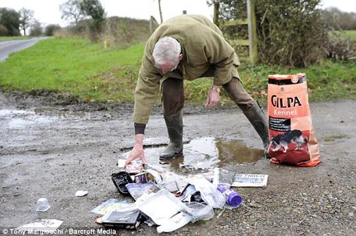 Một người đàn ông nhặt rác trên một con đường bên ngoài làng Caddington, gần Luton. (Nguồn: Daily Mail)