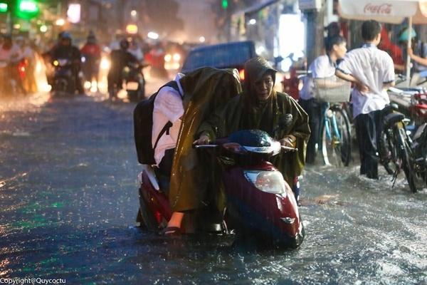 Bức ảnh cậu con trai ngồi phía sau, trong khingười mẹ lội nước ngập ngang đầu gối để đẩy xe trong cơn mưa từng nhận được nhiều sự chú ý cùng những bình luận tranh cãi gay gắtcủa cộng đồng mạng trong năm 2015. (Ảnh: Internet)