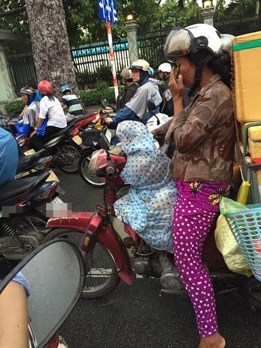 Nhiều người đã cảm thấy rất bất ngờ và cảm động trước bức ảnh người phụ nữđiều khiểnxe gắn máy trên đường Sài Gòn, chở lỉnh kỉnh đồ đạcđã chấp nhận chịu ướt, nhườngáo mưa của mình cho chú cún cưng. Trong khi đó, chú chó vẫn ngoan ngoãn ngồi phía trước xe để chủ chở về nhà. (Ảnh: Internet)