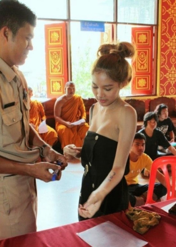 Một cô gái được chưa được sĩ quan ghi số thứ tự trên cánh tay.