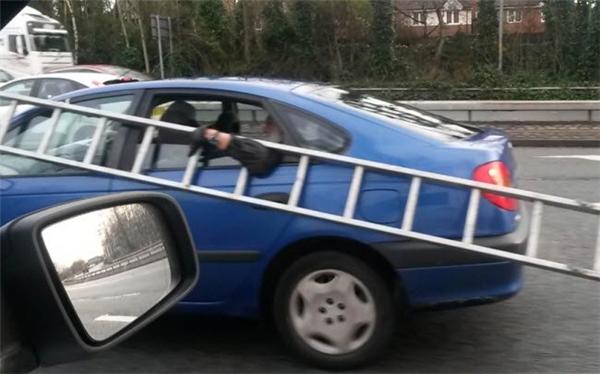 Người đàn ông vác theo chiếc thang dài trong khi ngôi ghế sau trong chiếc ô tô di chuyển trên đường ở thành phố Bolton, Anh.