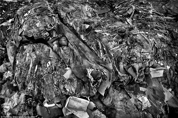 Nước màu trắng đen khiếnhình ảnh một thiếu niên nằm ngủtại một bãi rác ở Mombasa, Kenya càng khắc họa rõ hiện thực khắc nghiệt mà vô cùng ấn tượng. (Ảnh: Timothy Allen, Anh)