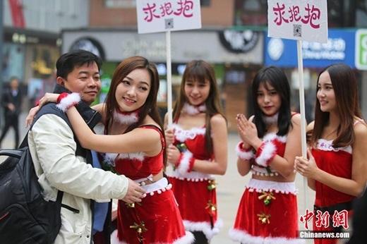 Một người đàn ông hạnh phúc khi được cô gái ôm. (Nguồn Chinanews.com)