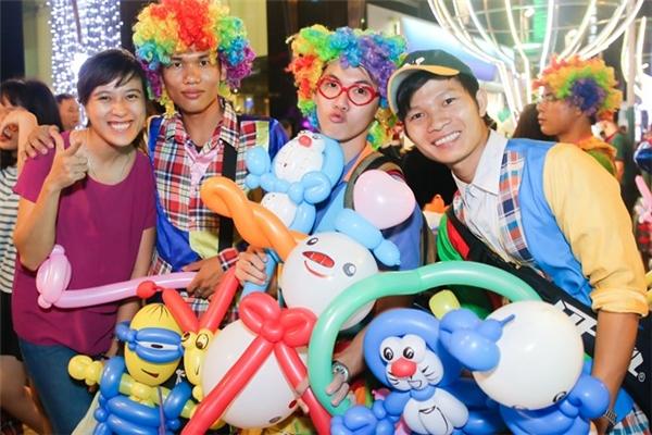 """4 bạn trẻ thuộc các nhóm """"Children Smile, Chú hề Wanbi, Những chú hề vui nhộn"""" đi bán bong bóng và đùa vui chụp ảnh lưu niệm với khách. Ảnh:Hải An."""