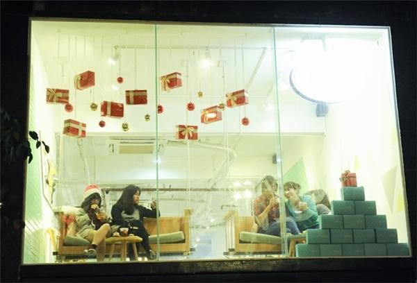 Thay vì chen lấn giữa dòng người tấp nập, các cô gái này lại chọn cho mình một quán cà phê có khung cảnh ngắm phố phường đẹp để tận hưởng không khí Noel. Ảnh:Việt Hùng.