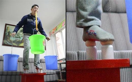 Võ sư Zuo Chongyang xách ba xô nước trong khi đứng trên 4 quả trứng ở thành phố Trường Sa, tỉnh Hồ Nam, Trung Quốc.