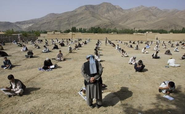 Tháng 7/2009, hình thức thi ngoài trời đã được áp dụng tại một ngôi trường ở làng Sangarkhel (Afghanistan). Học sinh ngồi thẳng hàng trên nền đất để làm bài thi cuối kì.(Ảnh Internet)