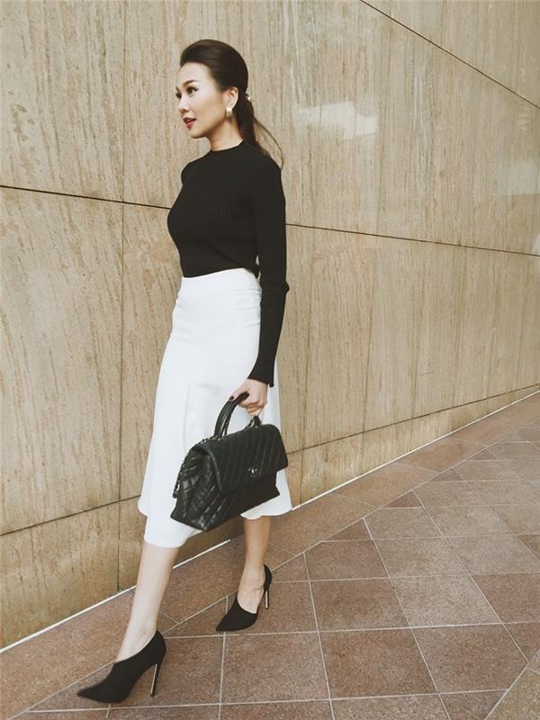 Mùa lạnh đầy nắng của miền Nam giúp các cô gái có thể chưng diện thoải mái, nhẹ nhàng hơn nhưng vẫn mang đậm hơi thở của thời trang Thu - Đông. Thanh Hằng kết hợp áo phông dài tay cùng chân váy điệu đà trên nền hai tông màu trắng, đen kinh điển. Tổng thể trở nên bắt mắt hơn nhờ giày cao gót có thiết kế khá lạ mắt cùng túi xách của Chanel.