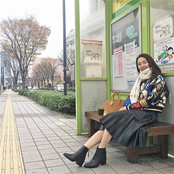 Bộ trang phục điệu đà của Minh Hằng trở nên cá tính hơn nhờ chiếc áo khoác thể thao với những họa tiết hoạt hình vui nhộn. Giày boots được kết hợp đồng điệu về chất liệu, màu sắc với chân váy xếp li hợp xu hướng.