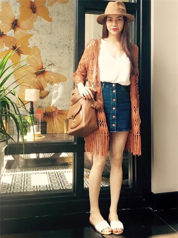 """Bắt nhịp xu hướng trang phục thập niên 1970, Hồ Ngọc Hà lăng xê mốt chân váy cài cúc trước, chất liệu denim. Set trang phục được ứng dụng khi xuống phố ngày hè. Trong ảnh, """"nữ hoàng giải trí"""" diện áo len cardigan bên ngoài, dép đế bệt thoải mái."""