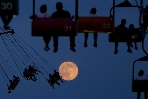 Khoảnh khắc trùng hợp này khiến người xem cảm giác con người sắp chạm đến mặt trăng xa xôi. Ảnh chụp tại công viên trò chơi State Fair Meadowlands, East Rutherford, New Jersey.