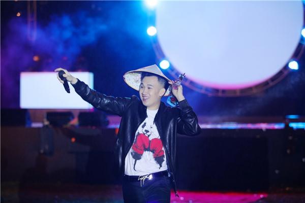 Trời mưa ngày càng lớn nên Dương Triệu Vũ phải mượn tạm chiếc nón lá của một khán giả để tiếp tục biểu diễn. - Tin sao Viet - Tin tuc sao Viet - Scandal sao Viet - Tin tuc cua Sao - Tin cua Sao