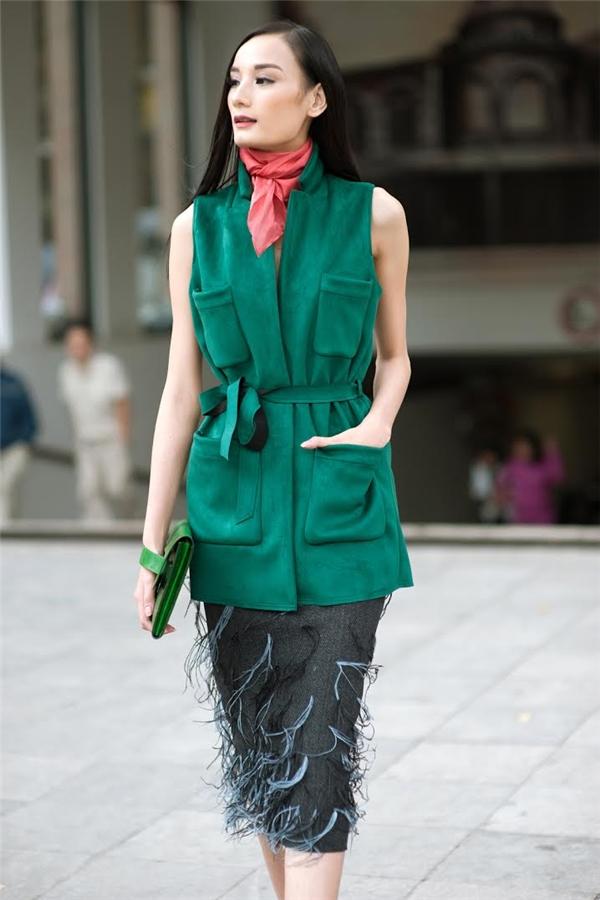 Cô chọn thiết kế tua rua đang thịnh hành nhất hiện nay đi kèm khăn cổ choàng giả nơ xinh xắn tô điểm nét hiện đại cho người mặc.