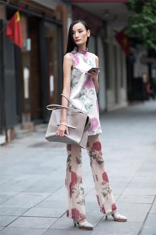 Phụ kiện đi kèm là chiếc túi xách to bản tông xuyệt tông cùng giày cao gót sành điệu.