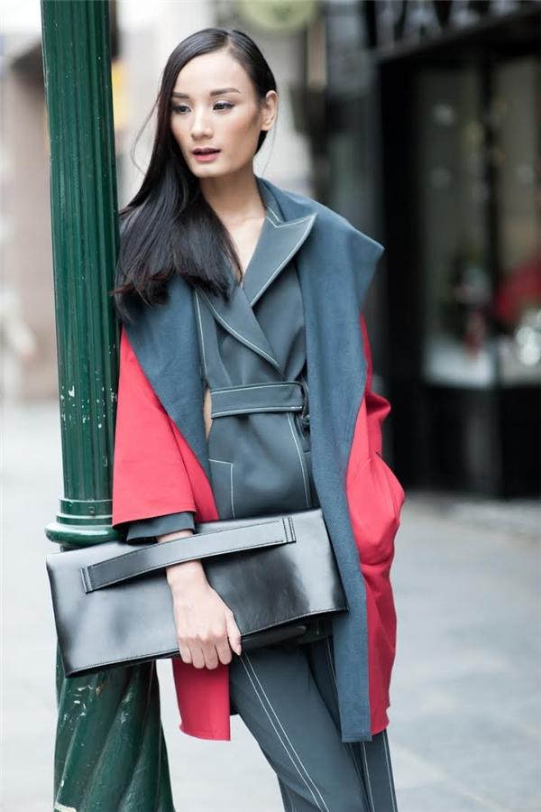 Kết hợp hài hòa giữa những gam màu nổi bật sáng tối, chiếc túi cầm tay với kiểu dáng lạ mắt chính là điểm cộng cho bộ trang phục này.