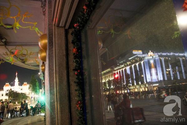 Trụ sở UBND TP.HCM và tòa nhà của một khách sạn những ngày cuối năm rực rỡ sắc màu, phản chiếu lung linh qua tấm gương.