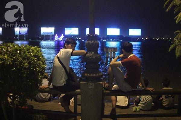 ... dù có bảng cấm nhưng nhiều bạn trẻ vẫn trèo qua lan can, ngồi bên bờ sông (Ảnh Khang Thái).