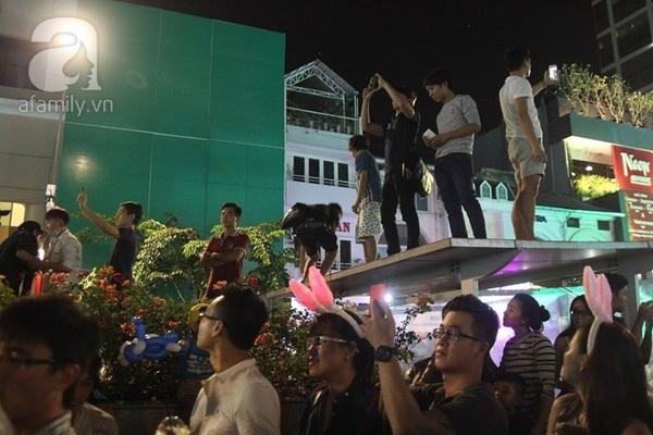 Khi màn bắn pháo hoa bắt đầu, một bộ phận giới trẻ trèo cả lên nóc trung tâm điều khiển phố đi bộ. (Ảnh Khang Thái).