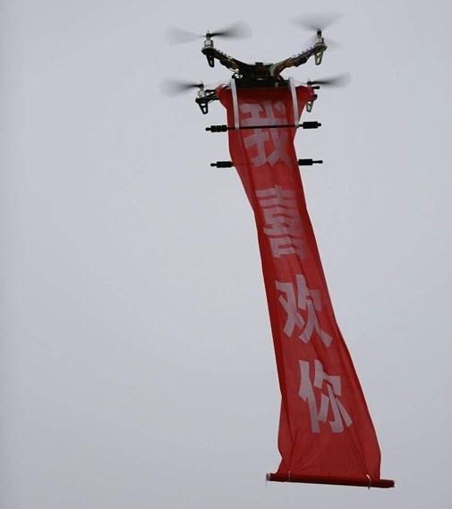 """Chiếc trực thăng thả xuống mảnh vải đỏ có ghi dòng chữ """"mình thích cậu"""". (Ảnh: Internet)"""