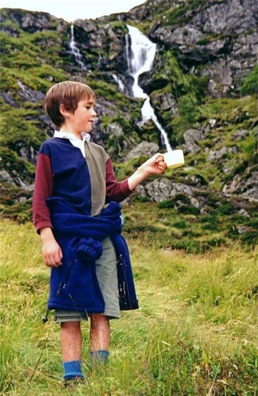 Cậu bé hứng lấy dòng suối chảy từ trên núi. (Ảnh: Internet)