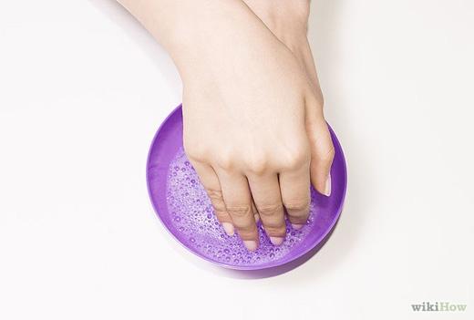 Ngâm tay vào nước ấm pha xà phòng hoặc ngâm tay vào dấm, keo sẽ từ từ bong ra, lúc này hãy lột bỏ lớp keo thật nhẹ nhàng. (Ảnh: Internet)