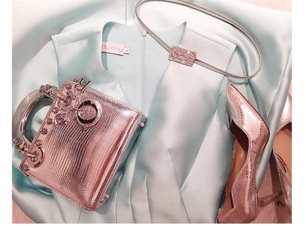 """Chiếc túi xách Dior màu ánh kim vừa được cô nàng """"rinh"""" về cách đây không lâu cũng có giá hơn 80 triệu đồng. Tùy theo màu sắc mà chiếc túi này có giá dao động đến khoảng 150 triệu đồng. Tổng thể tạo nên sự đồng điệu với giày cao gót ánh kim thanh mảnh."""