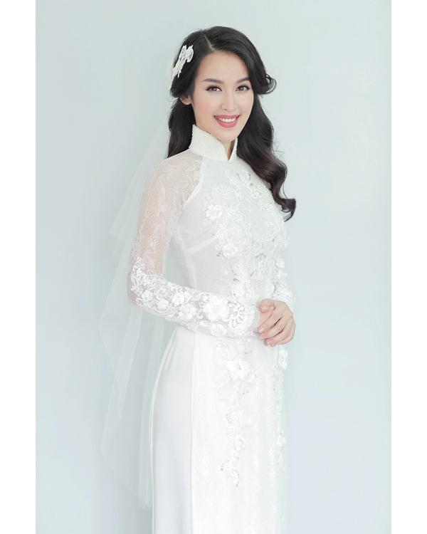 Trong ngày trọng đại, Tú Vi chọn áo dài với tông trắng tinh khôi, thanh khiết. Thiết kế tạo điểm nhấn bằng chi tiết ren đính kết đối xứng hai bên thân áo.