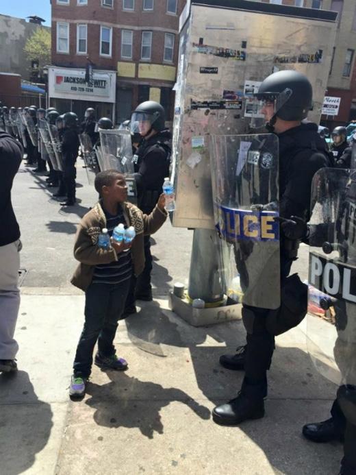 Cậu bé này đem nước cho cảnh sát trong một ngày nắng nóng. (Ảnh: Internet)