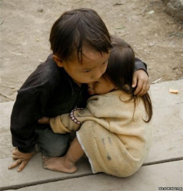 """Cậu bé người Hmong ở Hà Giang đang dỗ dành cô em gái nhỏ xíu của mình. """"Làm anh khó đấy, phải đâu chuyện đùa!"""", dù không lớn hơn em mình bao nhiêu nhưng tinh thần muốn chở che và yêu thương người thân của cậu bérất đáng khen ngợi. (Ảnh: Internet)"""
