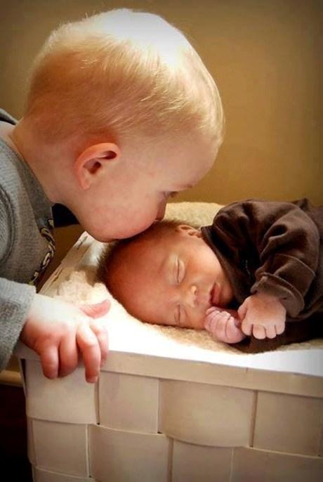 Cậu bé đặt một nụ hôn lên đứa em nhỏ xíu của mình. (Ảnh: Internet)