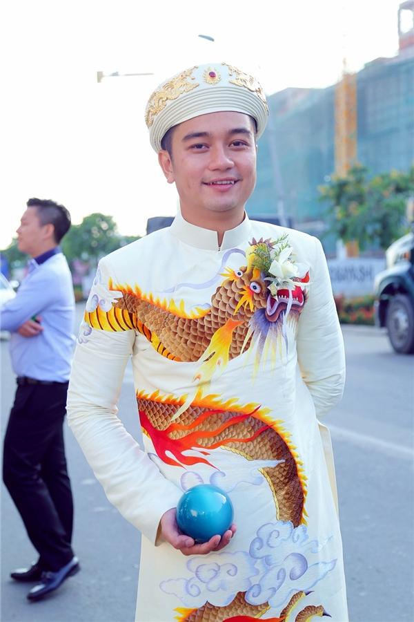"""""""Chàng rể"""" Hữu Quân diện chiếc áo dài thuê hình rồng bắt mắt. Anh cầm trên tay một quả cầu màu xanh thay cho hoa cưới. - Tin sao Viet - Tin tuc sao Viet - Scandal sao Viet - Tin tuc cua Sao - Tin cua Sao"""