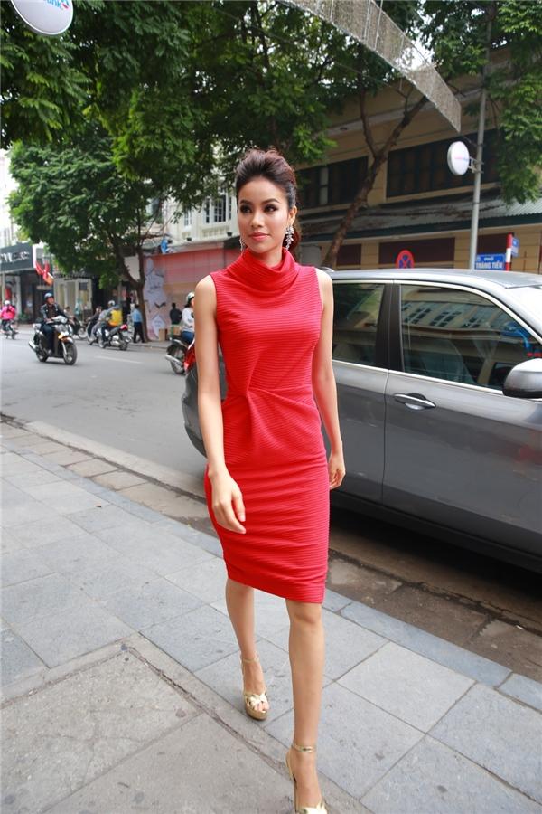 Cùng chọn sắc đỏ khi tham dự buổi nói chuyện với khán giả, người hâm mộ tại Hà Nội, Phạm Hương lại nhẹ nhàng, kín đáo hơn trong dáng váy cocktail truyền thống với những đường gấp nếp, dựng phom hiện đại, tinh tế. Cô kết hợp trang phục cùng bộ phụ kiện ánh kim nổi bật. Hoa hậu Hoàn vũ Việt Nam 2015 luôn được khen ngợi bởi gu thời trang hiện đại, gợi cảm, sang trọng.