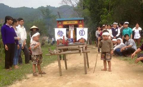 Hình ảnh hai emNguyễn Bá Tuấn và Nguyễn Bá Đứcchống gậy trên con đường đất tiễn mẹ về nơi an nghỉ cuối cùng. (Ảnh: Facebook)