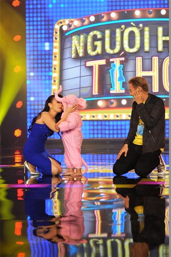 """Ở tập thi thứ 6, hóa thân chú voi hồng của Ku Tin được đánh giá là đáng yêu đến nỗi… giám khảo Cẩm Ly """"chịu không nổi"""" mà phải trực tiếp chạy lên sân khấu """"in dấu son"""" vào má em tận… 4 nụ hôn liên tiếp."""