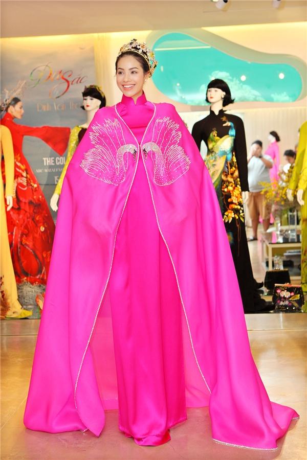 Phạm Hương diện bộ áo dài màu hồng nổi bật với dáng áo truyền thống bên trong kết hợp áo choàng bên ngoài. Thiết kế tạo điểm nhấn bởi họa tiết in thêu kì công được thực hiện bởi những người thợ có kinh nghiệm lâu năm trong nghề.