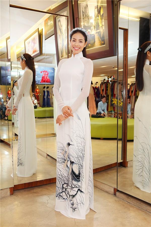 Người đẹp 24 tuổi sang trọng với họa tiết thêu màu xám trắng. Những phụ kiện đi kèm giúp bộ áo dài trở nên thu hút, bắt mắt hơn.