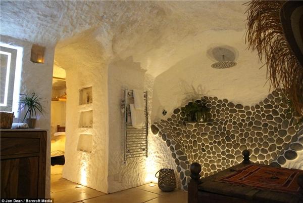 Bức tường được trang trí từ đá cuội mang đến vẻ sang trọng cho nhà tắm. Vòi hoa sen cùng giá mắc khăn tắm hiện đại càng làm nên giá trị của nội thất ngôi nhà.(Ảnh: Daily Mail)