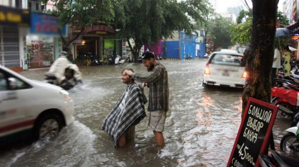 Một lần cắt tóc tại Việt Nam khác: giữa đường phố ngập nước. (Ảnh: Internet)