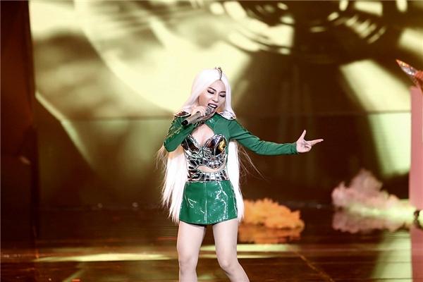Tuy nhiên, chỉ một tuần sau, Hằng Bingboong đã lột xác hoàn toàn với mái tóc màu trắng bạc cùng bộ jumpsuit màu xanh lá không thể nổi hơn. Những chi tiết ánh kim đi kèm giúp tổng thể trở nên thu hút trên sân khấu.