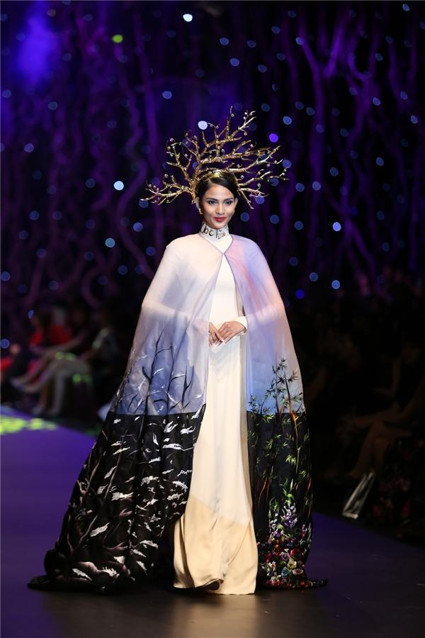 """350 triệu cũng là số tiền thu được trong phần đấu giá thiết kế mang tên """"Khúc giao mùa"""" kết hợp giữa áo dài trắng bên trong cùng áo choàng bên ngoài được tạo điểm nhấn bằng chi tiết thêu tay kì công, tỉ mỉ. Trương Thị May là người trình diễn thiết kế này."""