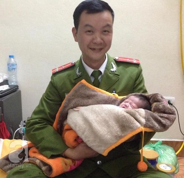 """Thượng úy Hoàng đang ôm ấp đứa bé trong sự yêu thương và chia sẻ với PV về cảm giác khi """"nhặt"""" được em ở gốc cây."""