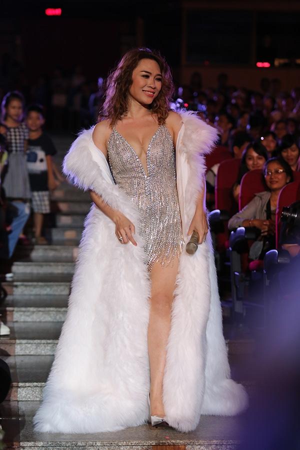 Đặc biệt khi diện bộ jumpsuit màu trắng bạc ánh kim, Mỹ Tâm còn mang thêm áo khoác lông to sụ mang đậm âm hưởng thời trang Thu - Đông. Đây cũng chính là xu hướng khá được ưa chuộng trên sân khấu biểu diễn của các ca sĩ trong thời gian gần đây.