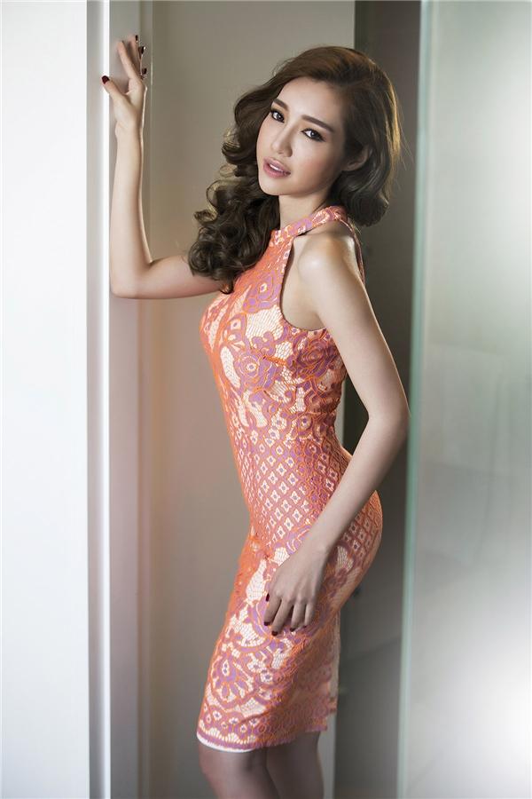 Elly Trần khoe khéo đường cong gợi cảm trong thiết kế bodycon có màu hồng pha cam trẻ trung, tươi mới. Thiết kế tạo điểm nhấn bởi những hoa văn được lồng ghép vào nhau một cách khéo léo.
