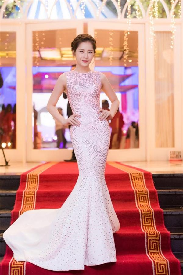 Chi Pu khoe dáng nuột nà cùng tỉ lệ cơ thể cân đối trong phom váy đuôi cá ôm sát do Lý Quí Khánh thực hiện. Thiết kế đơn giản được tạo điểm nhấn bằng những hạt đá đính kết với tông màu hồng nhạt sang trọng.